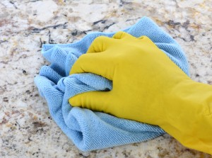 Closeup of a hand in a yellow latex glove using a blue towel to clean a granite counter top.