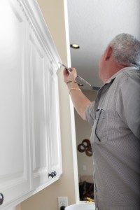 man in kitchen painting cabinet trim